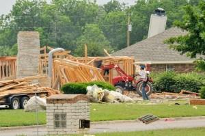 A demolition crew knocks down part of a house destroyed by the April 17 fertilizer plant explosion. Norman Lenburg/FEMA