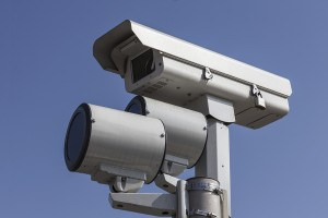 Stop light traffic camera with mounted strobe lights.