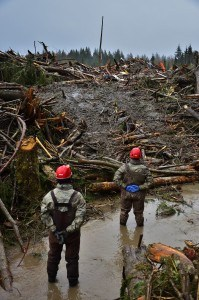 Tech. Sgt. Tayler Bates and Tech Sgt. Tony Rohrenbach, members of the Washington Air National Guard, 141 Civil Engineer Squadron pause for a moment of silence at 10:37 a.m., the same time that the mudslide occurred on Saturday March 22, 2014. Washington National Guard personnel continue to help the community of Oso in the wake of the mudslide. (U.S. Army photo by Staff Sgt. Rory Featherston FEMA news photo