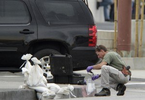 A Los Angeles FBI investigator collects evidence after a device worn by a bank manager was rendered safe by a bomb squad outside a Bank of America branch in East Los Angeles Wednesday, Sept. 5, 2012. (AP Photo/Damian Dovarganes)