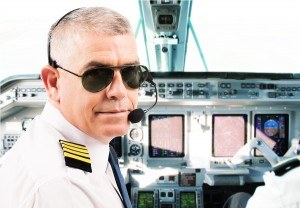 Airline pilot wearing uniform with epaulettes and headset workin