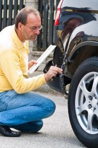 adjuster examining car damage