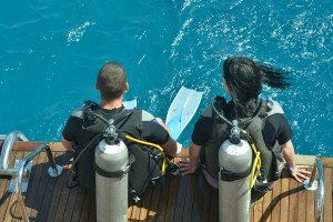 Two scuba divers preparing to dive into sea
