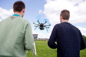 A pilot and photographer operating a UAV photography drone in an open field
