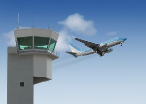 Airport tower with jet taking off in the background