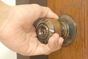 Closeup of male hand opening an old door knob