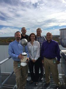 Amica employees Adam Kostecki (from left), Brian Leroux and Larry Brown (far right) with Nicole Homeier, vice president of Understory Weather, and Alex Kubicek, CEO of Understory Weather, with the RTi on the roof at Amica's corporate headquarters