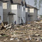 A resident of the Timberlea neighborhood looks over the damage of the area in Fort McMurray, Canada on June 2, 2016.  Residents started to return to the fire-damaged city in northern Alberta, cleaning up their homes and property. (Jason Franson/The Canadian Press via AP)