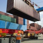 port worker supervising cargo containers uploading at dock